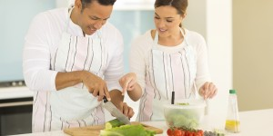 woman teaching husband cutting vegetables in kitchen